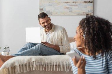 Afro-Amerikan kadının yanında, kablosuz kulaklıklı, bilgisayarını kullanan mutlu bir adam bulanık arka planda müzik dinliyor.