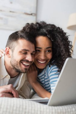 Positive interracial couple chilling on bed and watching movie on laptop stock vector