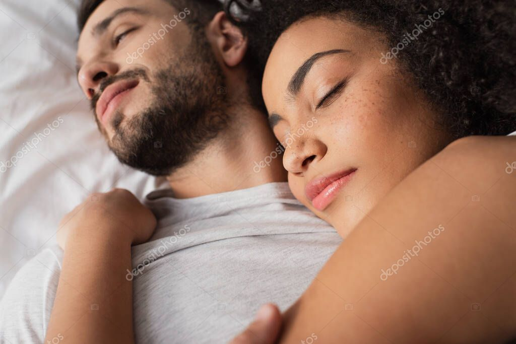 Close up of curly african american woman hugging bearded man and lying in bedroom stock vector