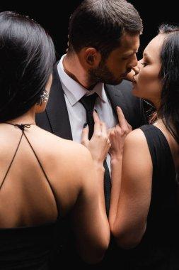 Seductive brunette women near businessman in suit isolated on black stock vector