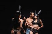 bruneta žena v králičí masce drží bičování bič v blízkosti milenců izolovaných na černé