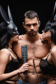 shirtless man looking at camera near passionate women in bunny masks isolated on black