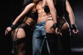 Teilansicht eines hemdlosen Mannes in Jeans mit Peitsche in der Nähe gefesselter Frauen auf schwarz