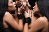 leidenschaftliche Frauen in Handschellen verführen jungen Mann ohne Hemd isoliert auf schwarz
