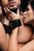 passionate women in handcuffs touching face of sexy man isolated on black