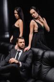 brunetky ženy v elegantních šatech dotýkají ramena podnikatele sedí na koženém gauči na černé