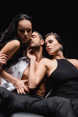Elegant, passionate women seducing man in unbuttoned shirt isolated on black stock vector