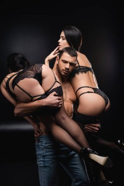 young man holding passionate women in lace lingerie on black background