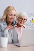 Fröhliche Frau umarmt Seniorin neben Laptop und Tasse im verschwommenen Vordergrund