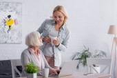 Usmívající se žena drží pohár v blízkosti matky a gadgets na stole