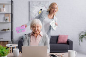 Senior woman using laptop near daughter with present and greeting card on blurred background