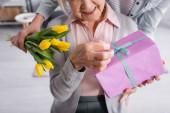 Vágott kilátás nő gazdaság virágok közelében idős anya jelen