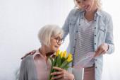 Usmívající se žena drží blahopřání v blízkosti starší matky se žlutými tulipány