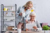 Žena s kelímkem ukazujícím na digitální tablet v ruce starší matky