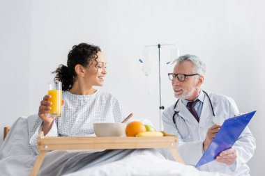 smiling doctor showing prescription to african american woman during breakfast in clinic