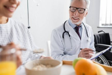 smiling doctor writing prescription near african american woman having breakfast on blurred foreground