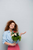 vidám nő néz fel, és mutató kézzel, miközben a kezében virágok szürke háttér