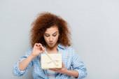 kíváncsi nő kockás ing nyitó ajándék doboz elszigetelt szürke