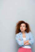 zaklatott nő áll keresztbe tett karokkal és duzzogó ajkak szürke háttér