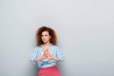 disgusted woman with curly hair showing stop gesture on grey background