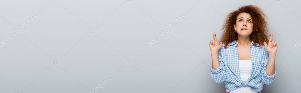 Tense woman with crossed fingers looking up on grey background, banner stock vector