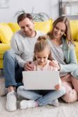 Dítě pomocí notebooku v blízkosti usmívající se rodiče na rozmazaném pozadí doma