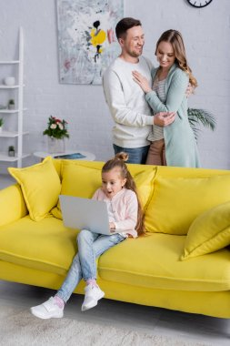 Amazed kid using laptop near cheerful parents hugging at home stock vector