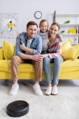 Usmívající se dítě objímající rodiče v blízkosti robotického vysavače na podlaze