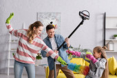 Positive family playing with cleaning supplies at home
