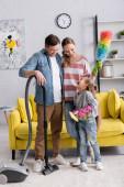 Usmívající se rodiče dívají na dceru s detergentem a hadrem doma
