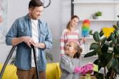 Lány takarító üzem és nézi apa porszívó otthon