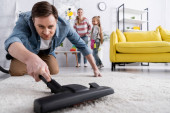 Mann putzt Teppich im verschwommenen Vordergrund bei verschwommener Familie zu Hause