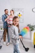 Child with dust brush looking at camera near parents and vacuum cleaner