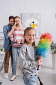 Pozitivní dítě drží prach štětec v blízkosti rodičů s vysavačem na rozmazaném pozadí