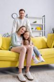 Nő ölelés gyerek a sárga kanapén közel mosolygós férj