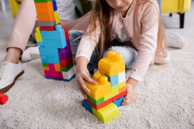 Cropped view of child playing building blocks near mother on carpet stock vector