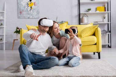 Woman hugging husband and daughter in vr headsets on floor at home stock vector