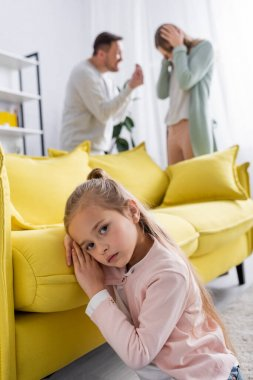 Girl looking at camera near couch and parents having conflict on blurred background stock vector