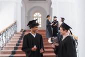 Lächelnder afrikanisch-amerikanischer Absolvent mit Diplom steht neben Freund und zeigt Ja-Geste an der Universität