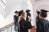Usmívající se absolvent v čepici držící diplom poblíž mezirasových přátel na univerzitě