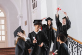 Excited graduate pointing at diploma near interracial friends