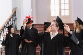 Šťastný starý mládenec při pohledu na diplom v blízkosti multietnických studentů