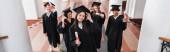 Vysoký úhel pohledu veselých multietnických studentů držících diplomy, banner