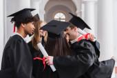 Mezirasoví studenti s diplomy objímající na univerzitě