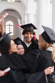 Veselí multietničtí studenti s diplomy na vysoké škole