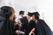 Low angle view of happy multiethnic graduates with diplomas in university hall