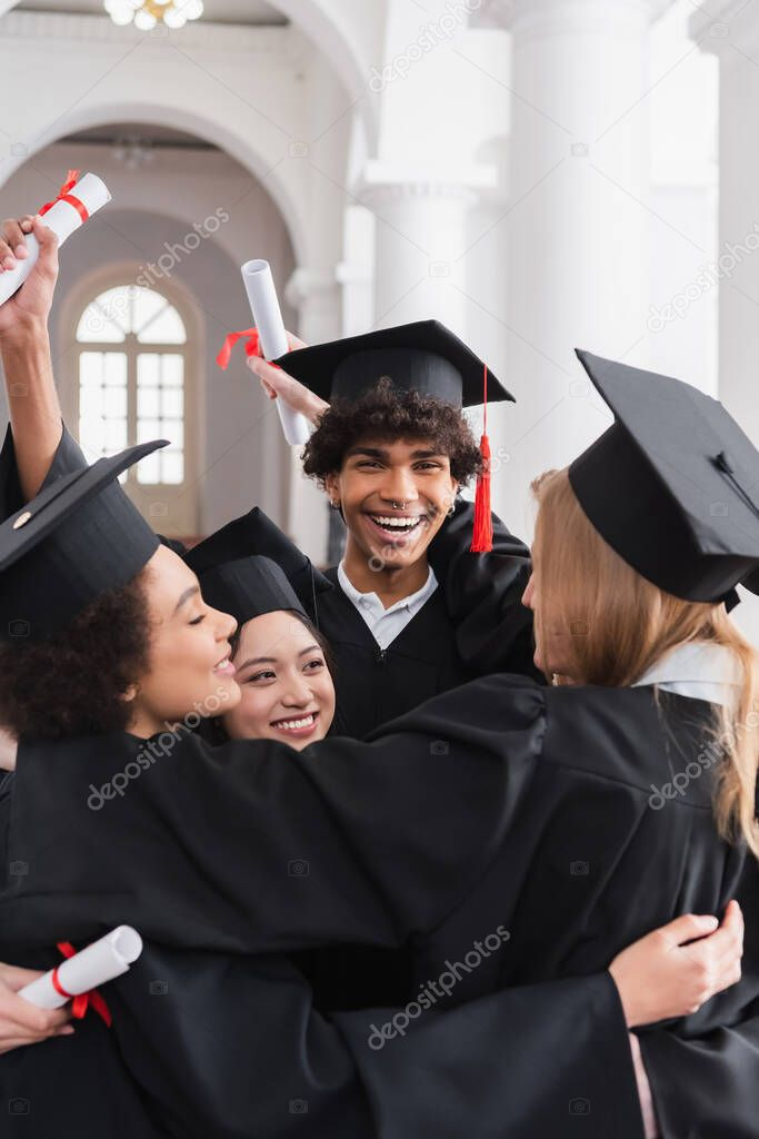 Cheerful multiethnic students with diplomas embracing in university stock vector