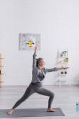 žena středního věku ve sportovním oblečení stojící v válečnické póze při cvičení jógy