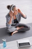 Hochwinkelaufnahme einer Frau mittleren Alters in drahtlosen Kopfhörern, die meditiert, während sie im Lotus auf einer Yogamatte in der Nähe des Laptops posiert