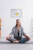 boldog középkorú nő ül lótuszban pózol jóga szőnyegen